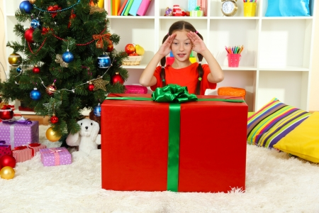 Little girl with large gift box near christmas tree photo