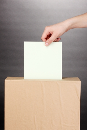 voting ballot: Hand with voting ballot and box on grey background