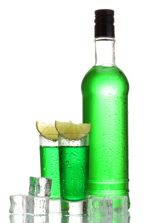 intoxicate: bottle and glasses of absinthe with lime and ice isolated on white