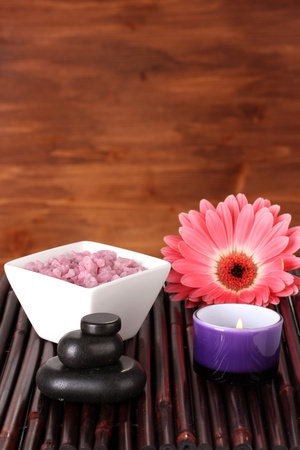 Composition of spa stones, bath salt, candle and gerbera on bamboo mat on wooden background photo