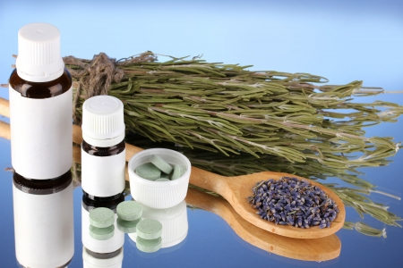 botanical remedy: bottles of medicines and herbs on blue background. concept of homeopathy
