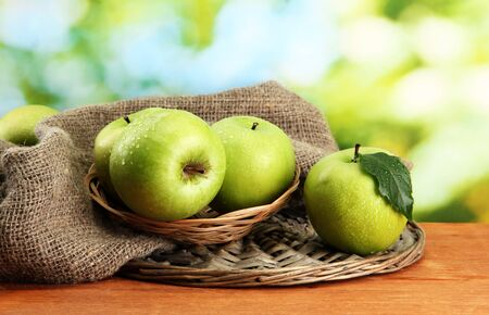 Ripe green apples in basket on burlap, on wooden table, on green background Stock Photo - 16593752