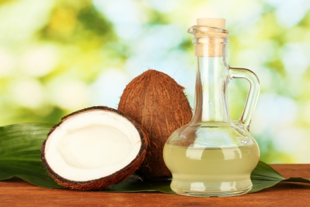 oil palm: decanter with coconut oil and coconuts on green background Stock Photo