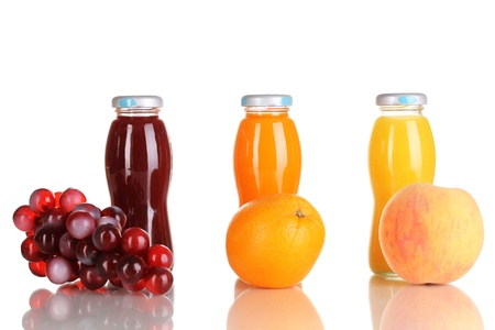 Delicious grapes, orange and apple juice in glass bottle and fruit next to it isolated on white photo