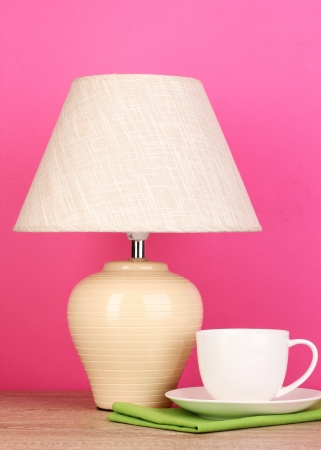 table lamp and cup on pink background photo