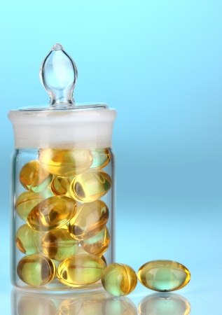 Capsules in receptacle on blue background photo