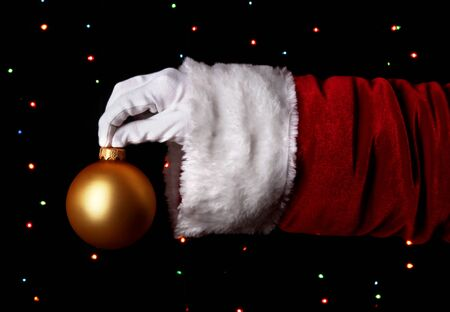 Santa Claus hand holding christmas ball on bright background Stock Photo - 16576056
