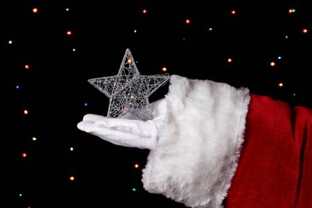 Santa Claus hand holding christmas star on bright background Stock Photo - 16576828
