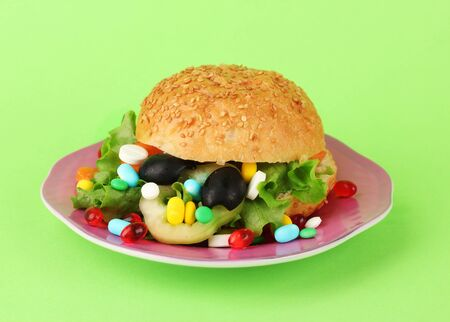Conceptual image for nutritional care:assorted vitamins and nutritional supplements in bun.On color background photo