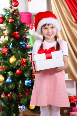 festively: Little girl with Christmas toys in festively decorated room