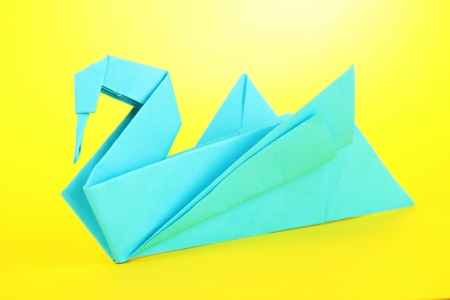 Origami swan on yellow background  photo