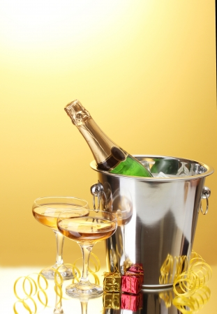 Champagne bottle in bucket with ice and glasses of champagne, on yellow background Stock Photo - 16591831