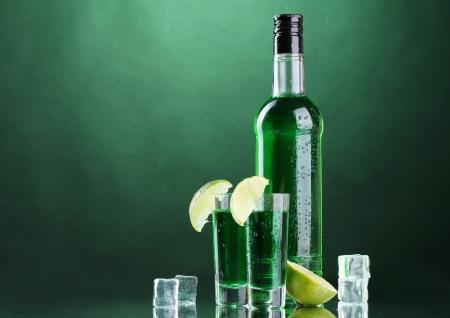 ajenjo: botella y las copas de absenta con limón y hielo sobre fondo verde