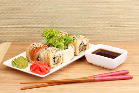 Tasty rolls served on white plate with chopsticks on wooden table on light background photo