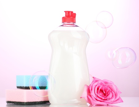 Dishwashing liquid with sponges and flower on pink background Stock Photo - 16566119