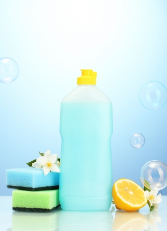 Dishwashing liquid with sponges and lemon with flowers on blue background Stock Photo - 16566124