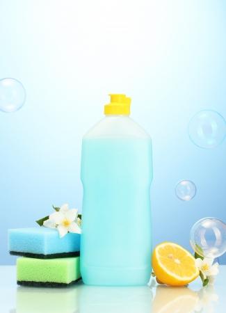 Dishwashing liquid with sponges and lemon with flowers on blue background Stock Photo - 16566124