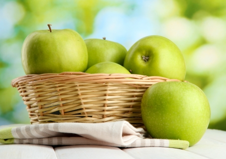 Ripe green apples with leaves in basket, on wooden table, on green background Stock Photo - 16566208