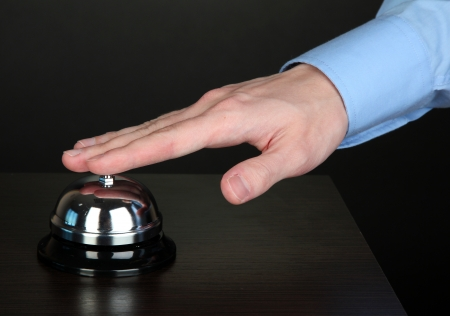 Hand ringing in service bell on wooden table on black background Stock Photo - 16566183