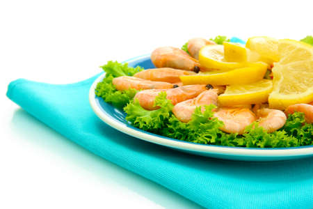 Boiled shrimps with lemon and lettuce leaves on plate, isolated on white photo