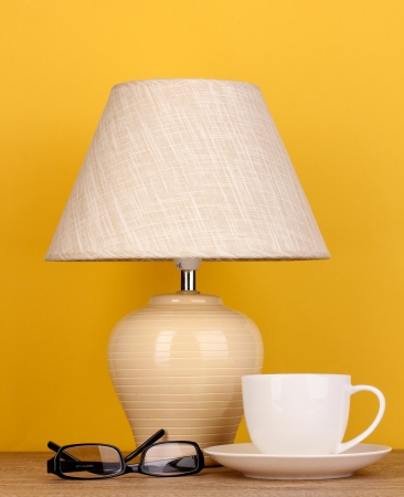 table lamp with cup and glasses on yellow background Stock Photo - 16566398