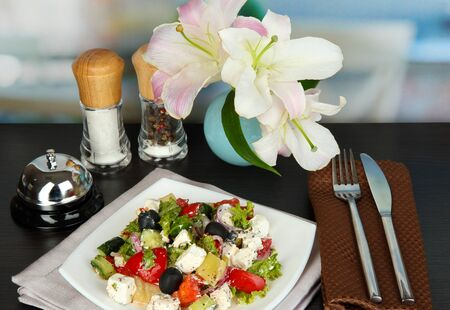 Fresh greek salad on white plate on table on restaurant background photo