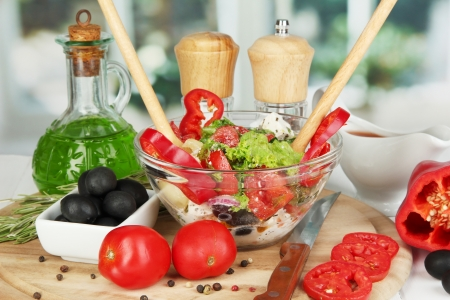 Fresh greek salad in glass bowl surrounded by ingredients for cooking on wooden table on window background photo