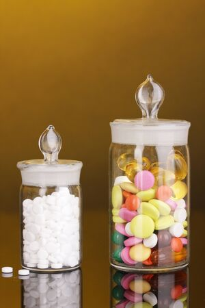 Capsules and pills in receptacles on orange background Stock Photo - 16566408