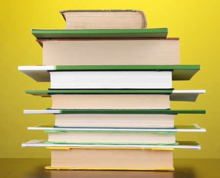 Stack of interesting books and magazines on wooden table on yellow background photo