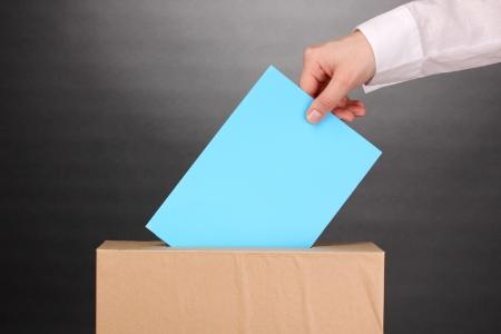 Hand met stembiljet en doos op grijze achtergrond