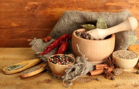 vijzel: mortel, kommen en lepels met kruiden, op houten achtergrond Stockfoto