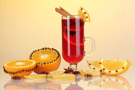 Fragrant mulled wine in glass with spices and oranges around on yellow background photo