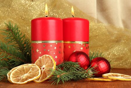 Two candles and christmas decorations, on golden cloth background photo