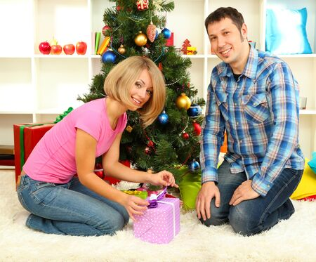 Young happy couple with presents sitting  near Christmas tree at home photo