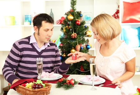 Young happy couple with presents sitting   at table near Christmas tree photo