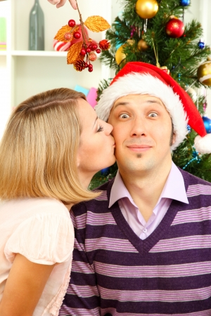 Romantic kiss under mistletoe photo
