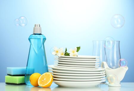 empty clean plates and glasses with dishwashing liquid, sponges and lemon on blue background photo