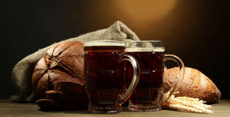 tankards of kvass and rye breads with ears, on wooden table on brown background photo