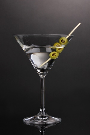 Martini glass and olives on grey background photo