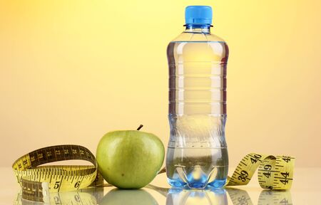 Bottle of water, apple and measuring tape on orange background photo