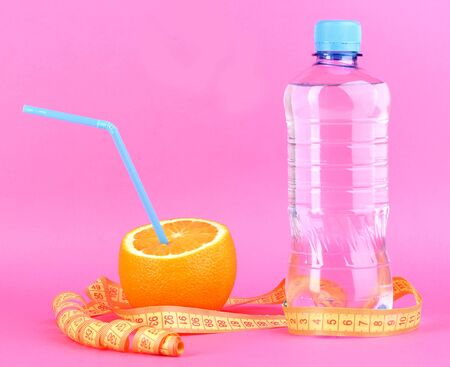 Ripe oranges and bottle of water as symbol of diet on pink background photo