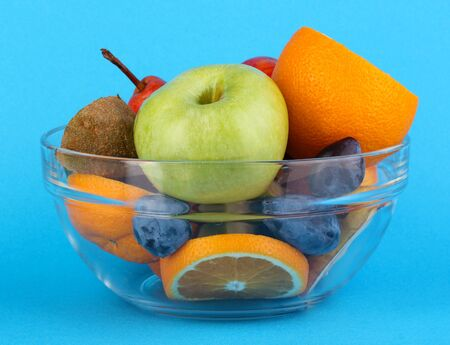 Glass bowl with fruit for diet on blue background Stock Photo - 16591013