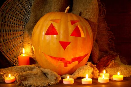 halloween pumpkin and candles, on wooden background photo