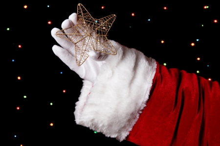 Santa Claus hand holding christmas star on bright background Stock Photo - 16591595