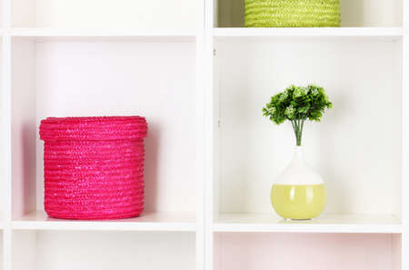 Color wicker boxes on cabinet shelves photo