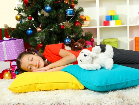 Little girl sleeping near christmas tree Stock Photo - 17129849