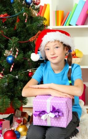 Little girl holding gift box near christmas tree Stock Photo - 17129848