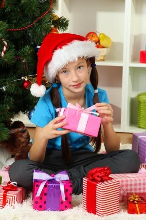 Little girl holding gift box near christmas tree Stock Photo - 17129852