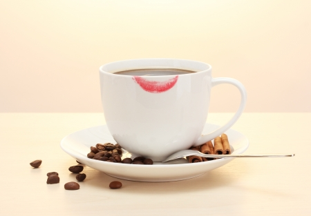 cup of coffee with lipstick mark beans and cinnamon sticks on wooden table photo