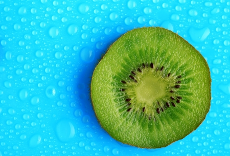 Slice of kiwi with drop on blue background photo